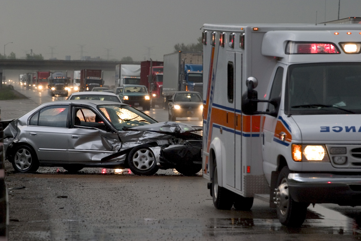 Car crash on major highway during rainfall at night. Ambulance in foreground and police car in background.